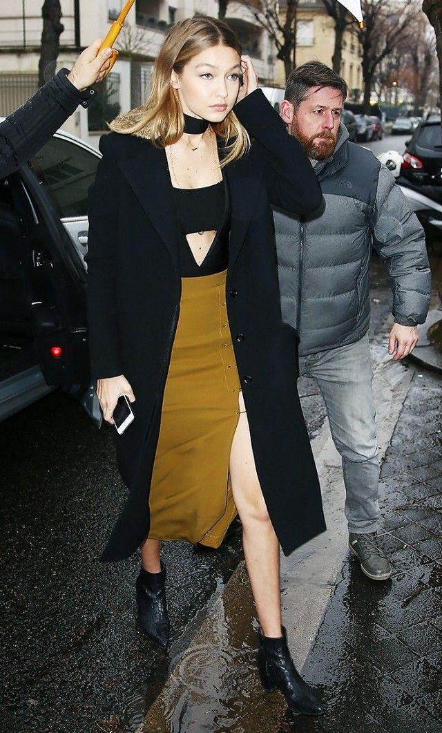 20bbf87c47efbd Gigi Hadid wears a cutout bodysuit, choker, long black coat, high-slit  skirt, and ankle boots