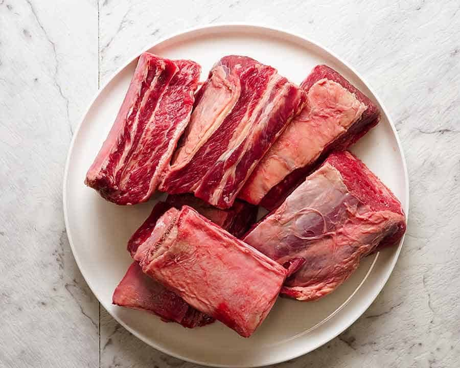 Two Beef Short Ribs Unseasoned Raw One Rib Shown At A Cross Section Bbq Beef Short Ribs Bbq Beef Bbq Beef Ribs