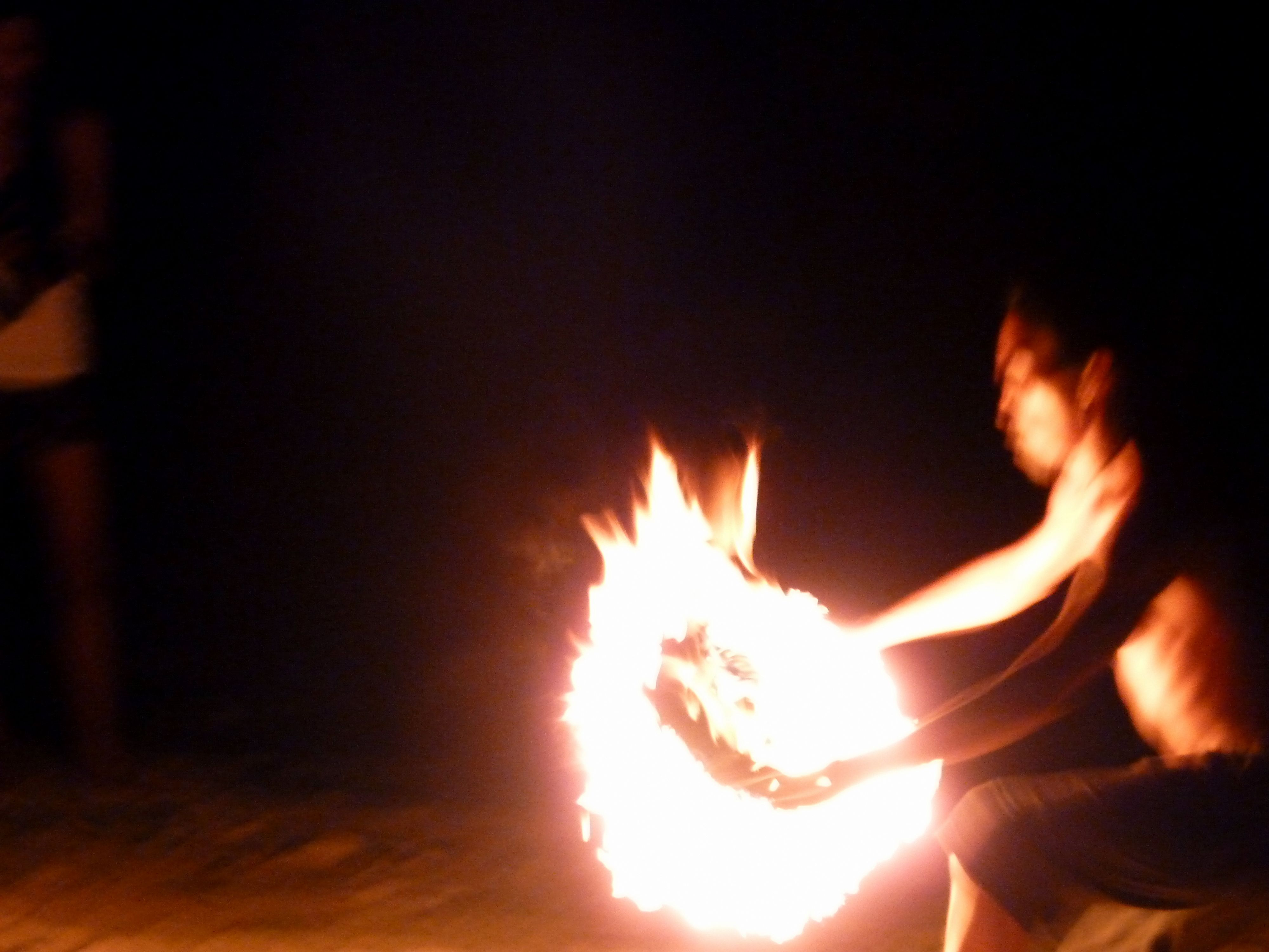a dancer plays with fire... in front of the iconic oops bar, alona beach, panglao, bohol, the philippines...