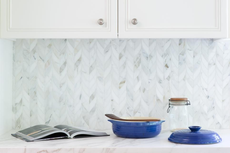 This light and bright kitchen features a marble tile ...