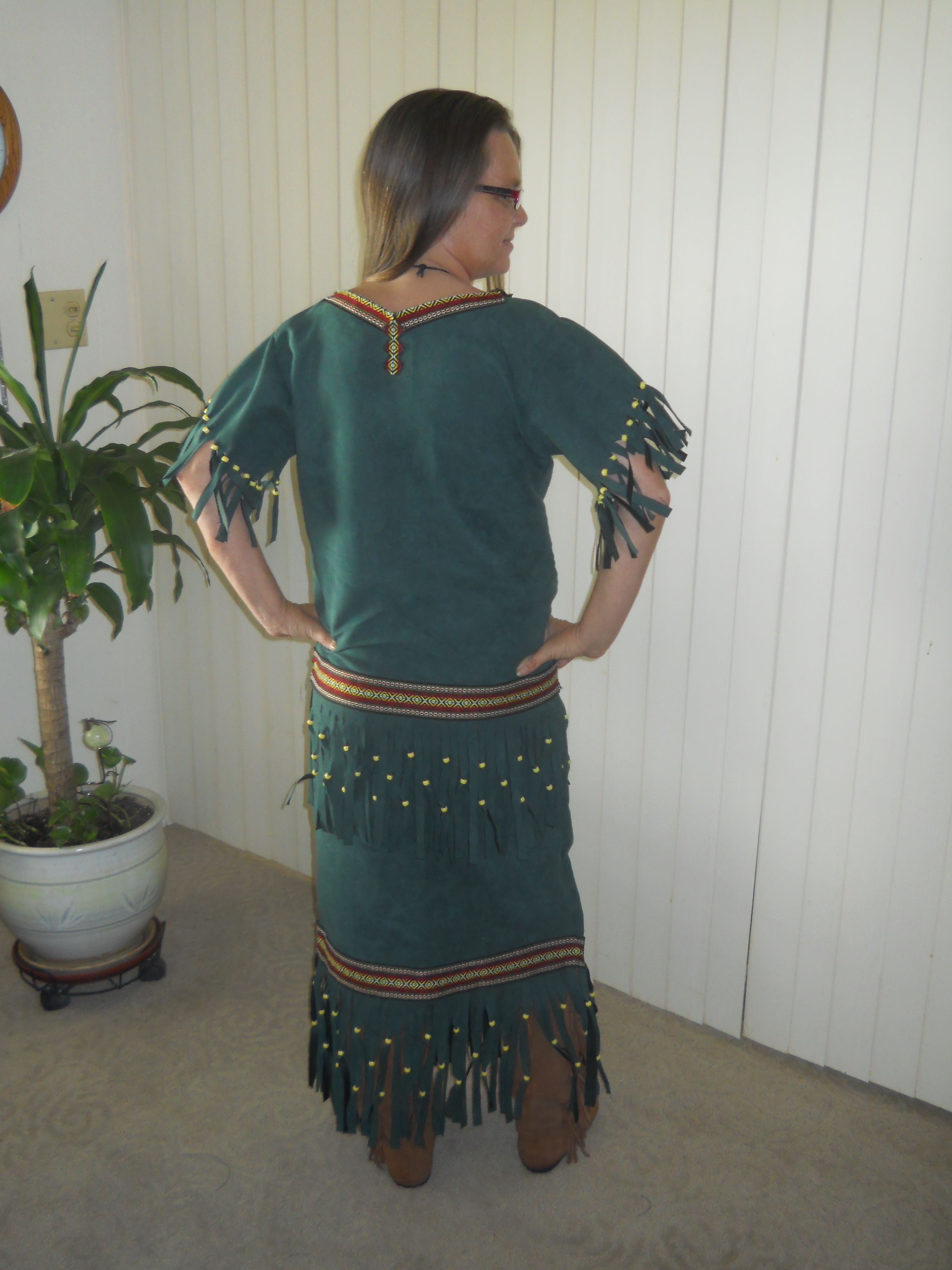 This is a 2 piece set that includes a drawstring style skirt with matching top that has a low waist line and fringed at the sleeve around bottom of top and bottom of skirt and adorned with beads...can be made out of buckskin (shown here in a faux suede)