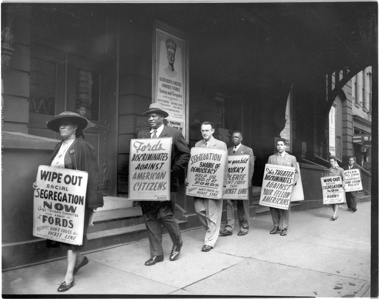Activists walk in a picket line holding NAACP Baltimore ...