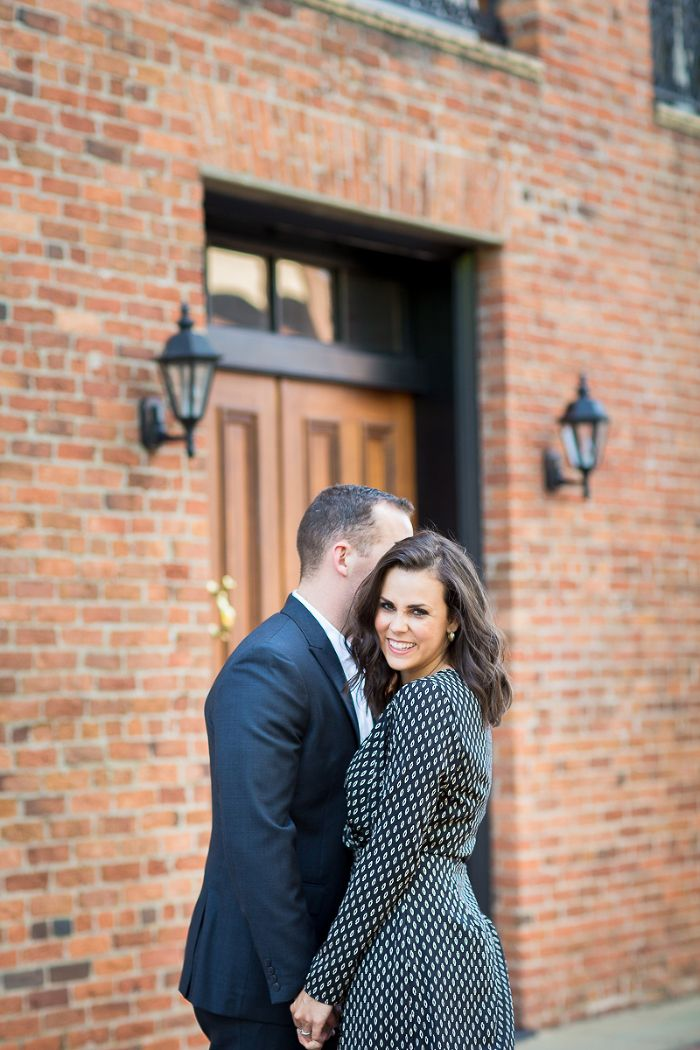 Uptown Columbus Georgia couple smiles in front of rustic brick building for wedding announcement photo | www.hannahandrandall.com