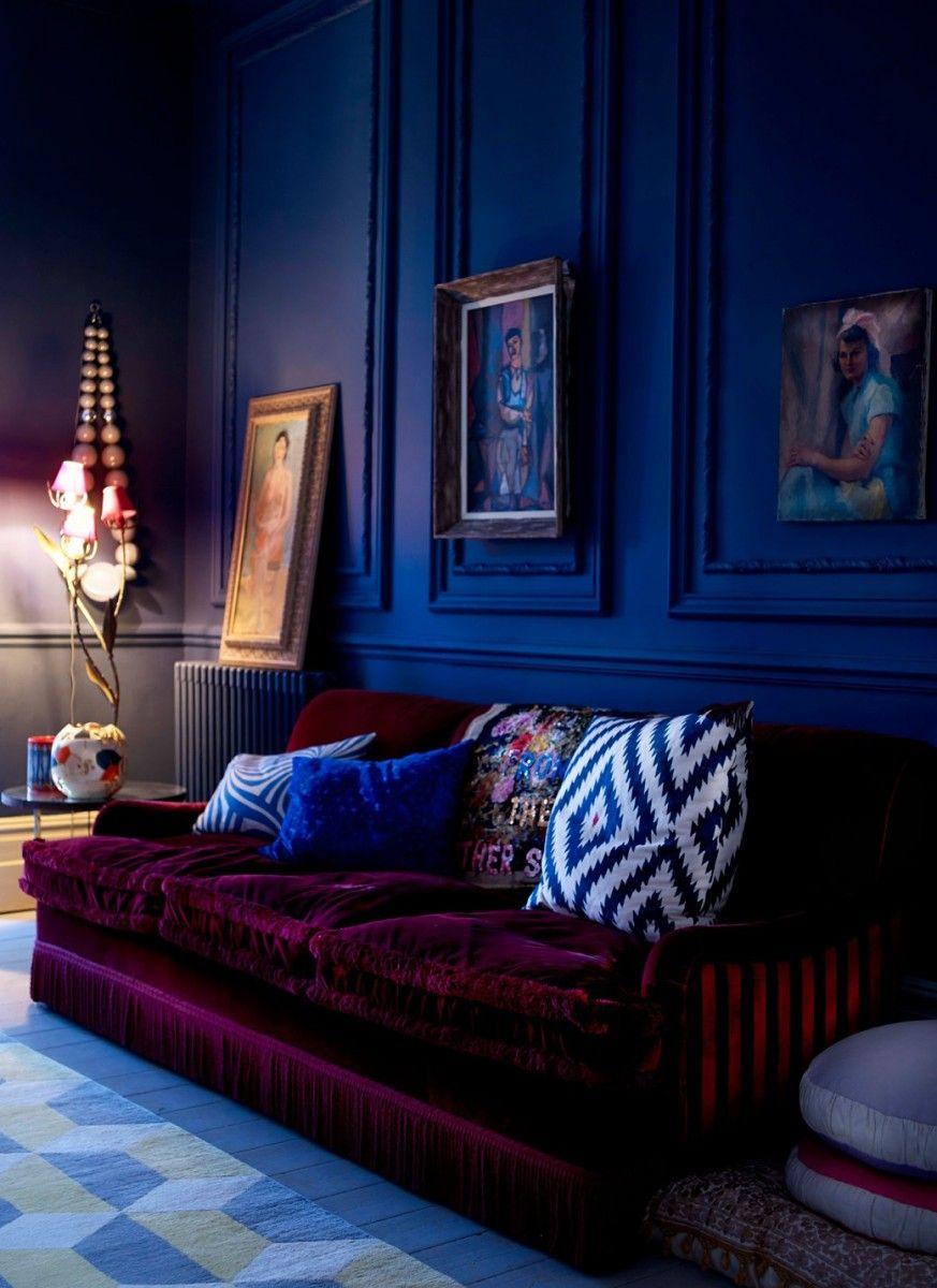 Royal blue walls and deep plum sofa give this room drama