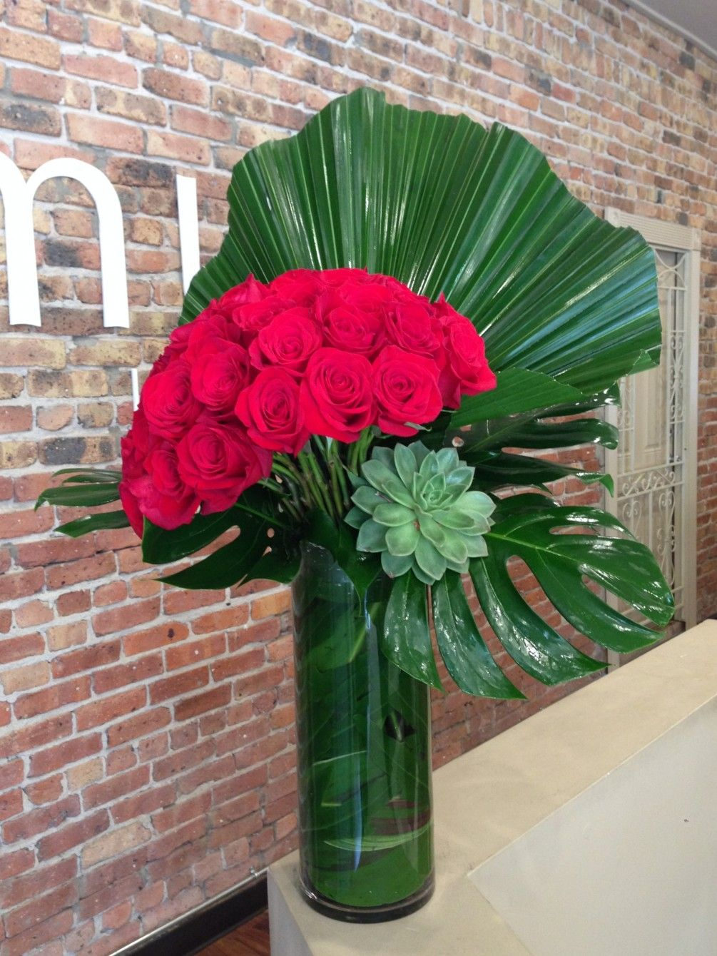 A leaning bouquet of 50 premium, long stemmed red roses