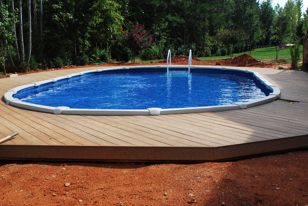 Above ground built into ground with wooden deck http for Swimming pool deck