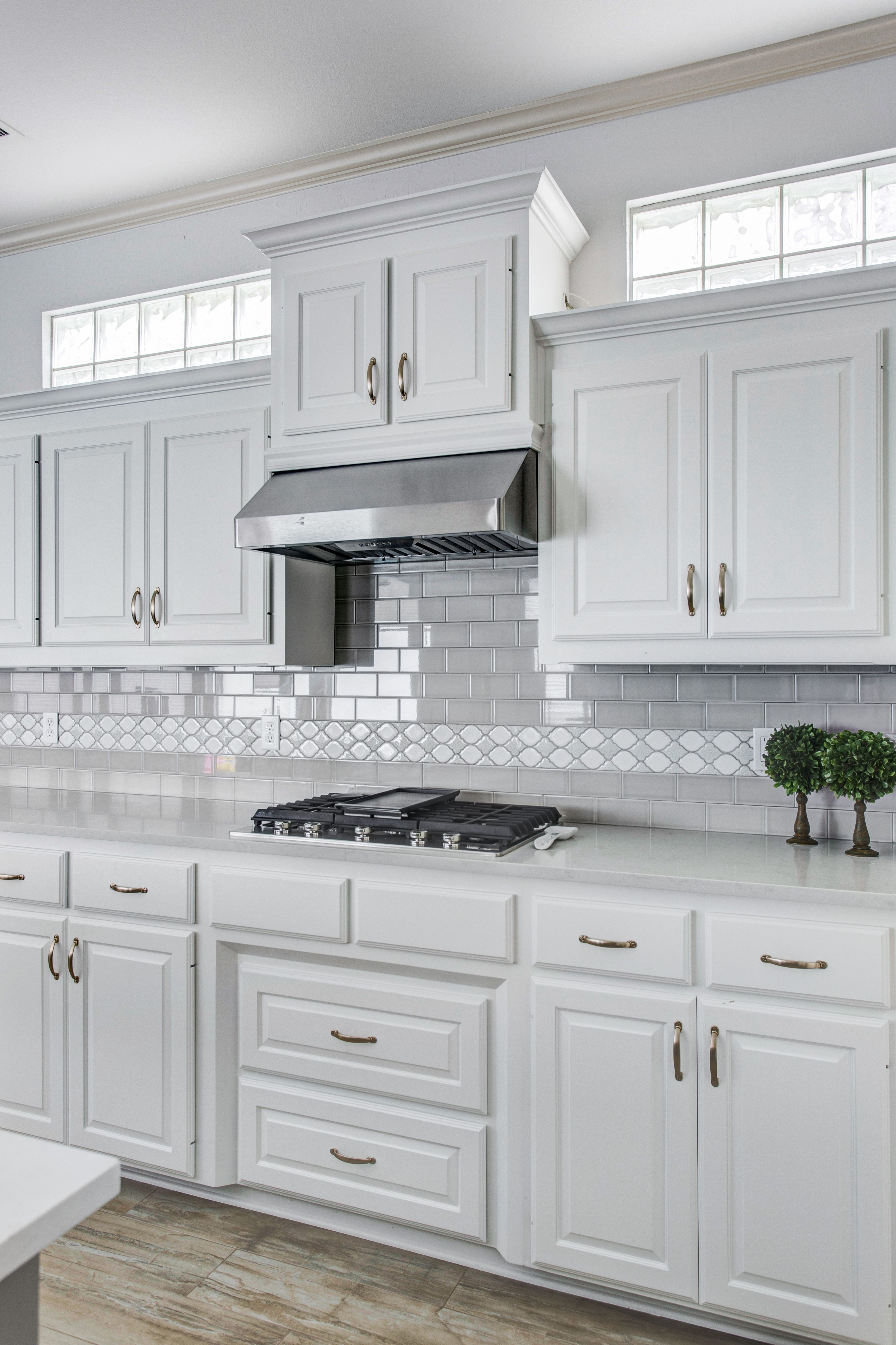Grey and white kitchen. White cabinets with grey subway ...