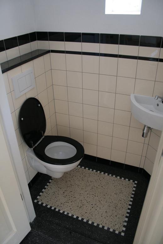 jaren 30 huis met gerenoveerd toilet, zwarte tegels met afgerodne bovenzijde, granito vloer   My