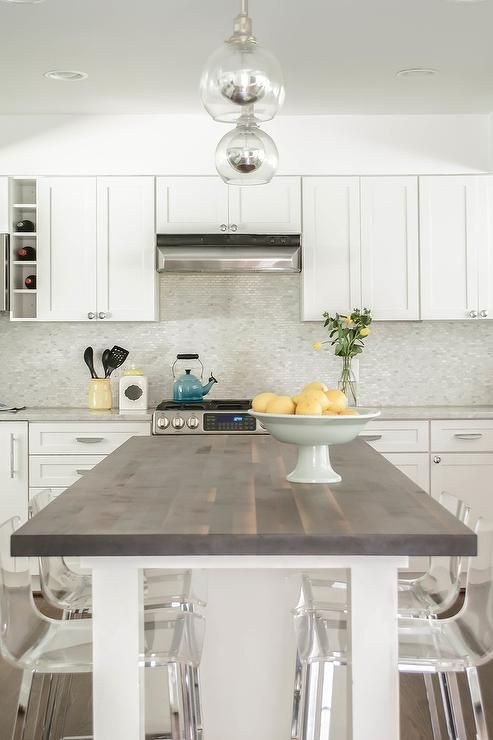 White Kitchen Island With Butcher Block Top two glass dome pendants hang over a white kitchen island topped