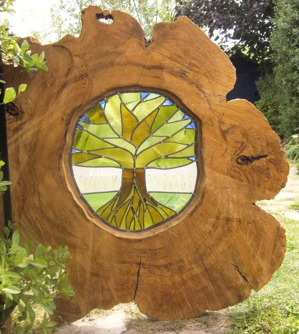 Stained glass tree made from recycled wine bottle glass inserted into tree bole - slice taken from tree root.