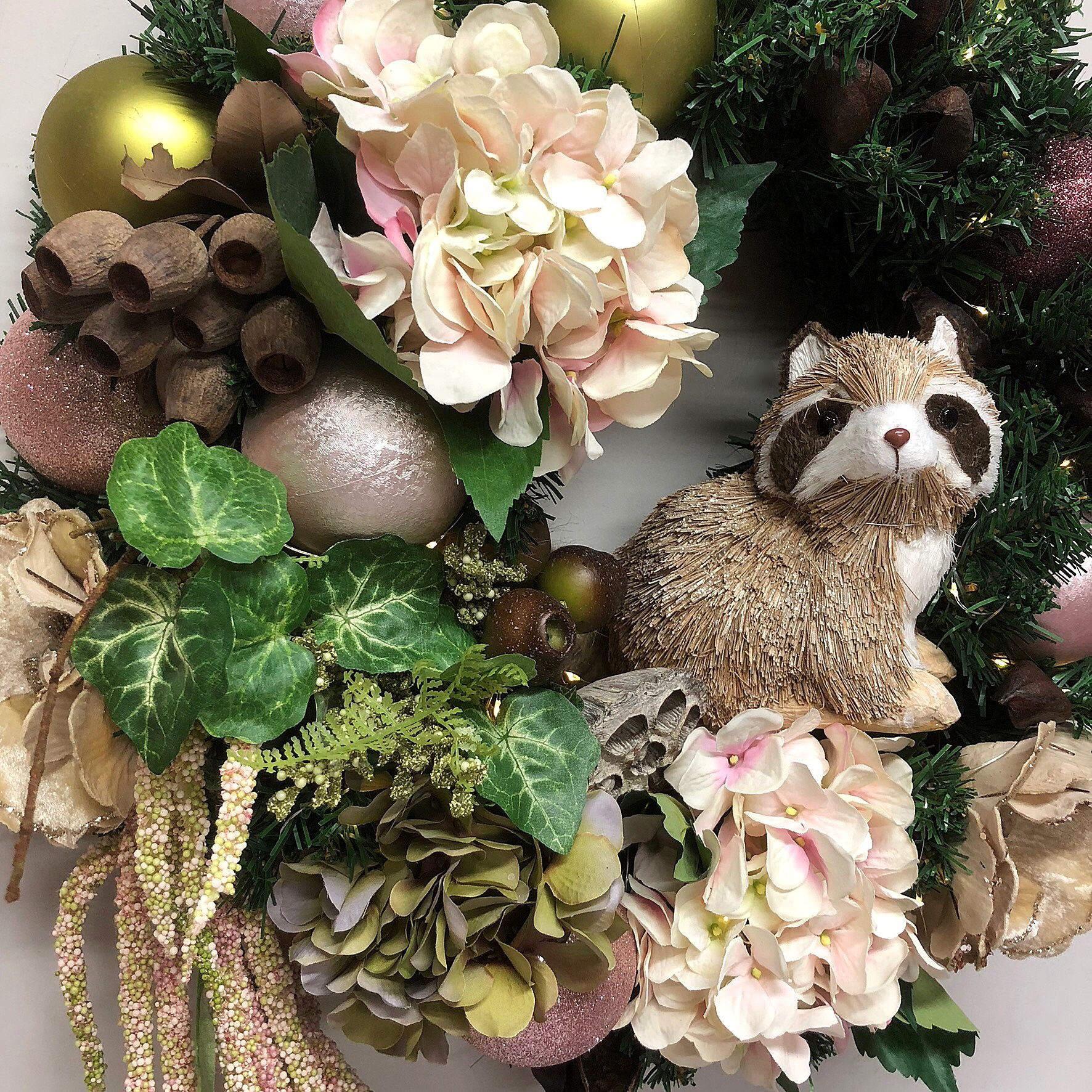 Garden wreath with friendly raccoon. Floral wreath