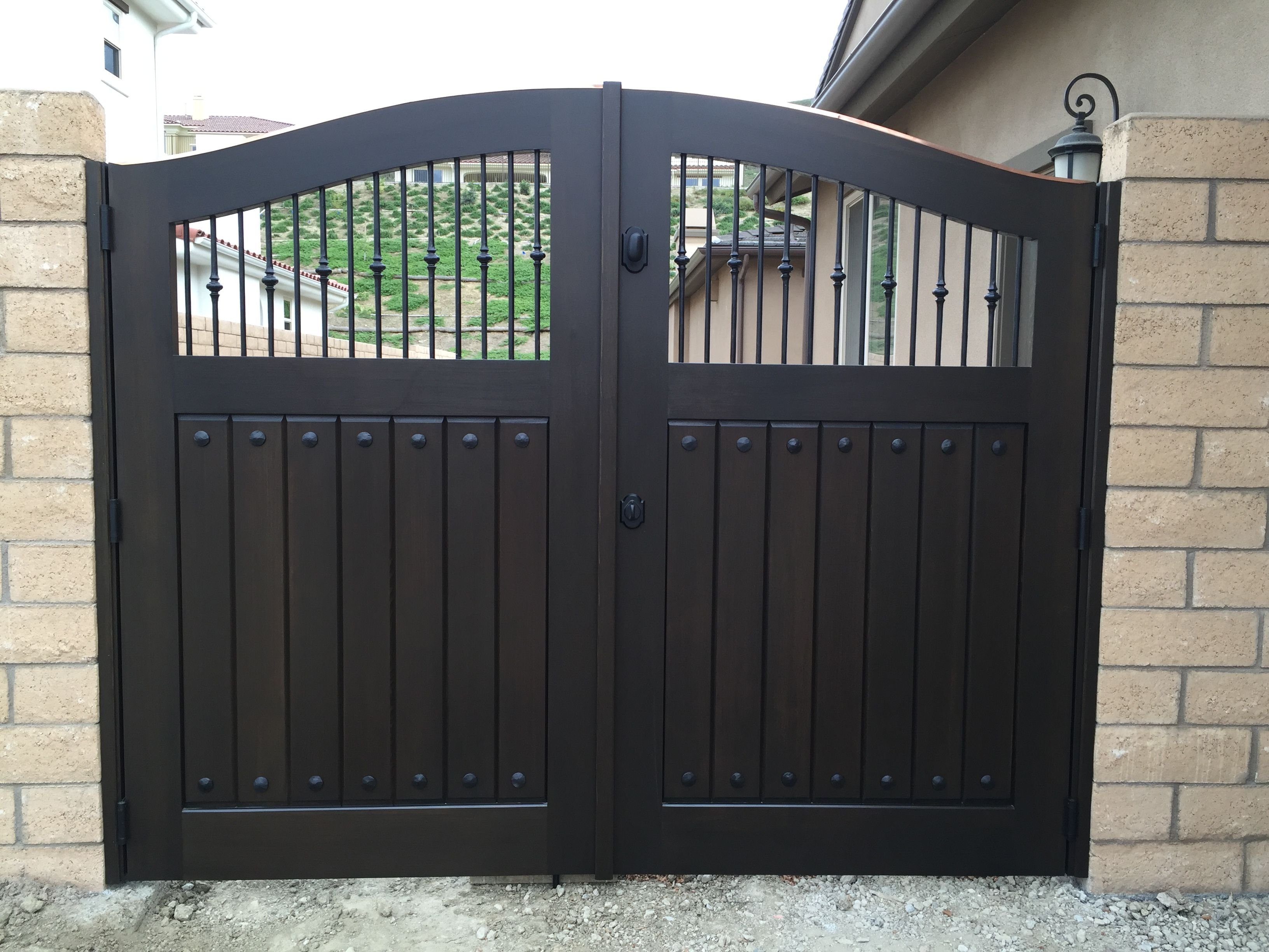 custom wood gate with swooping arch and decorative metal pickets