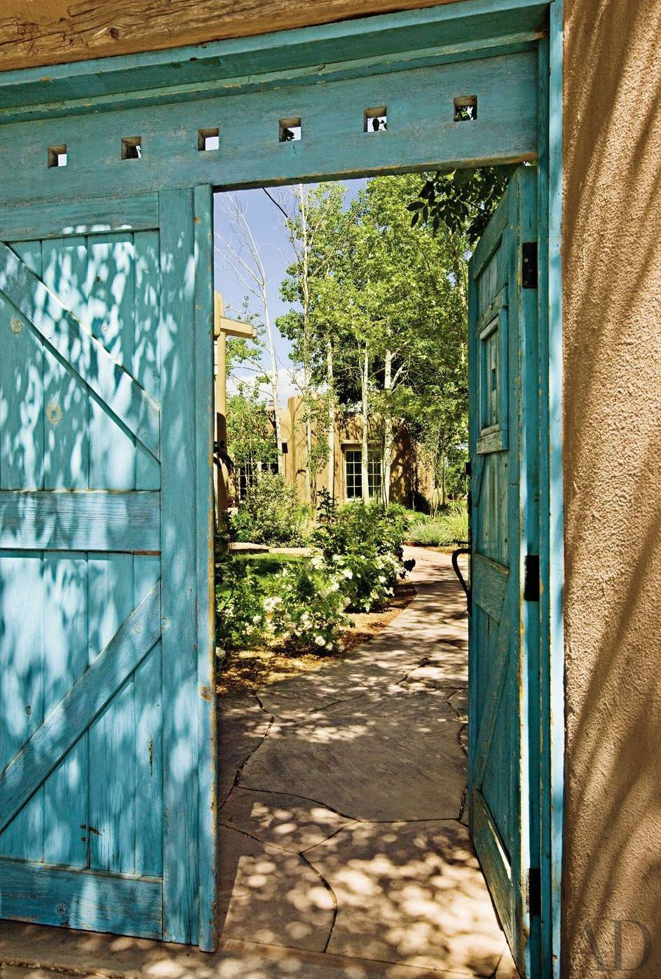 Behind the high walls and front gate of a downtown Santa Fe, New Mexico, adobe compound, a flagstone path leads to the main house.