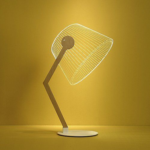 """The Studio Cheha Ziggi LED Lamp makes beautiful light out of illusion. The """"shade"""" is actually a 2-dimensional plate of acrylic glass, and the instant the warm LED light is turned on, the shade becomes a 3-dimensional design. The result is entirely intriguing to witness, instantly adding originality to your desktop setting. The acrylic shade is supported with an angled Birch arm and white metal base."""