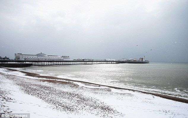 White scene: Brighton beach and pier were pictured today after heavy snowfalls overnight and this morning
