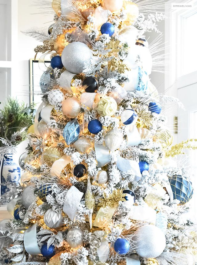 flocked christmas tree with navy light blue silver and gold ornaments christmas flocked. Black Bedroom Furniture Sets. Home Design Ideas