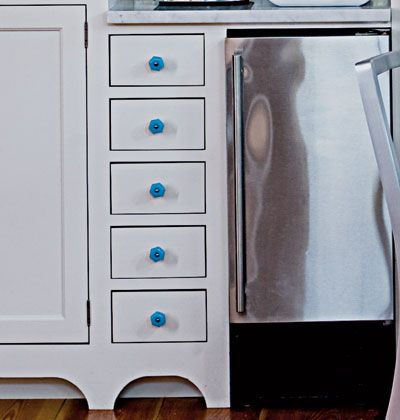 Instead of your run-of-the-mill brushed chrome cabinet knobs, choose brightly colored hardware that injects personality into the room. The cerulean blue against a white background is reminiscent of cool swimming pools on hot days.