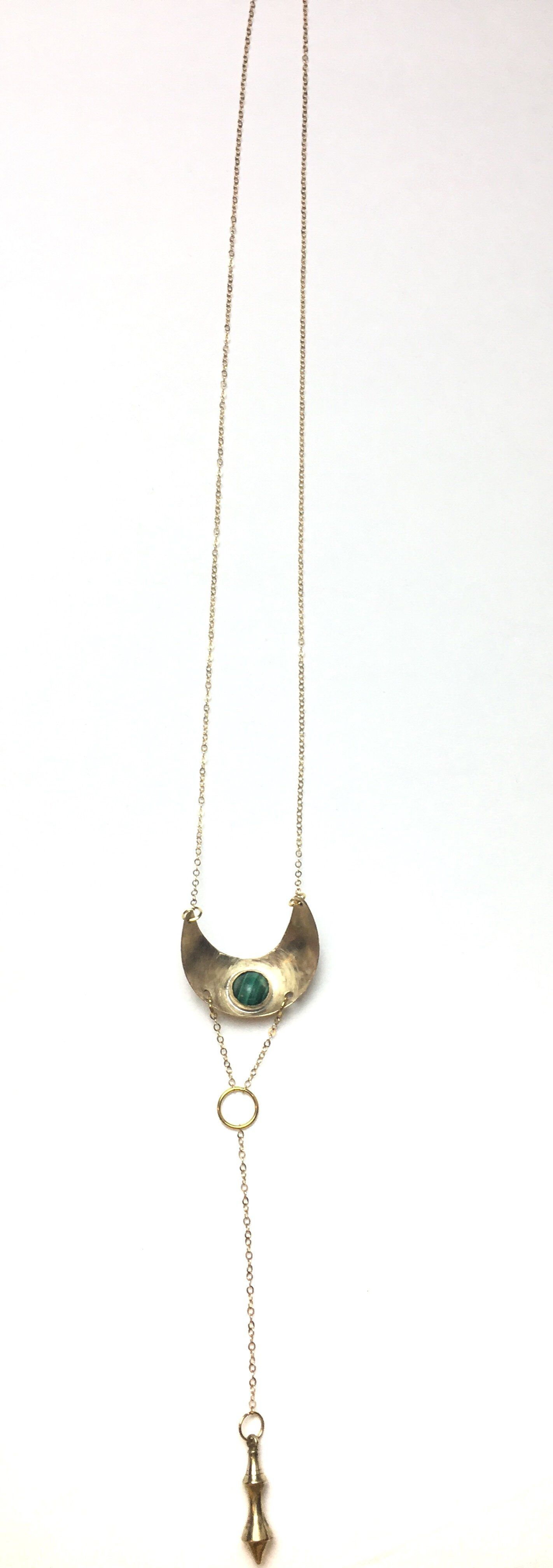 Inspired by the beauty and mystery of pendulums Made with Gold Filled chain, a Brass domed moon pendant, Malachite and Raw Brass pendulum that is plated in 14K Gold Falls above the belly button We encourage our lovers to use the Malachite Pendulum Lariat Necklace as a pendulum during a healing session or ritual. We love pendulums and their spiritual significance; they are often used as spiritual healing and inner growth tools. Pendulums promote healing with the process of dowsing, which seeks ou
