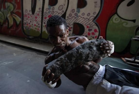 Aspiring boxer Chibata uses a rock for abdominal exercises during a training session at a gymnasium under the Alcantara Machado viaduct in the Mooca neighborhood of Sao Paulo, March 28, 2011.   REUTERS-Nacho Doce