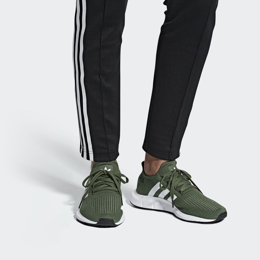 db1107c8e1bfb adidas Originals Swift Run shoes in base green worn on feet.