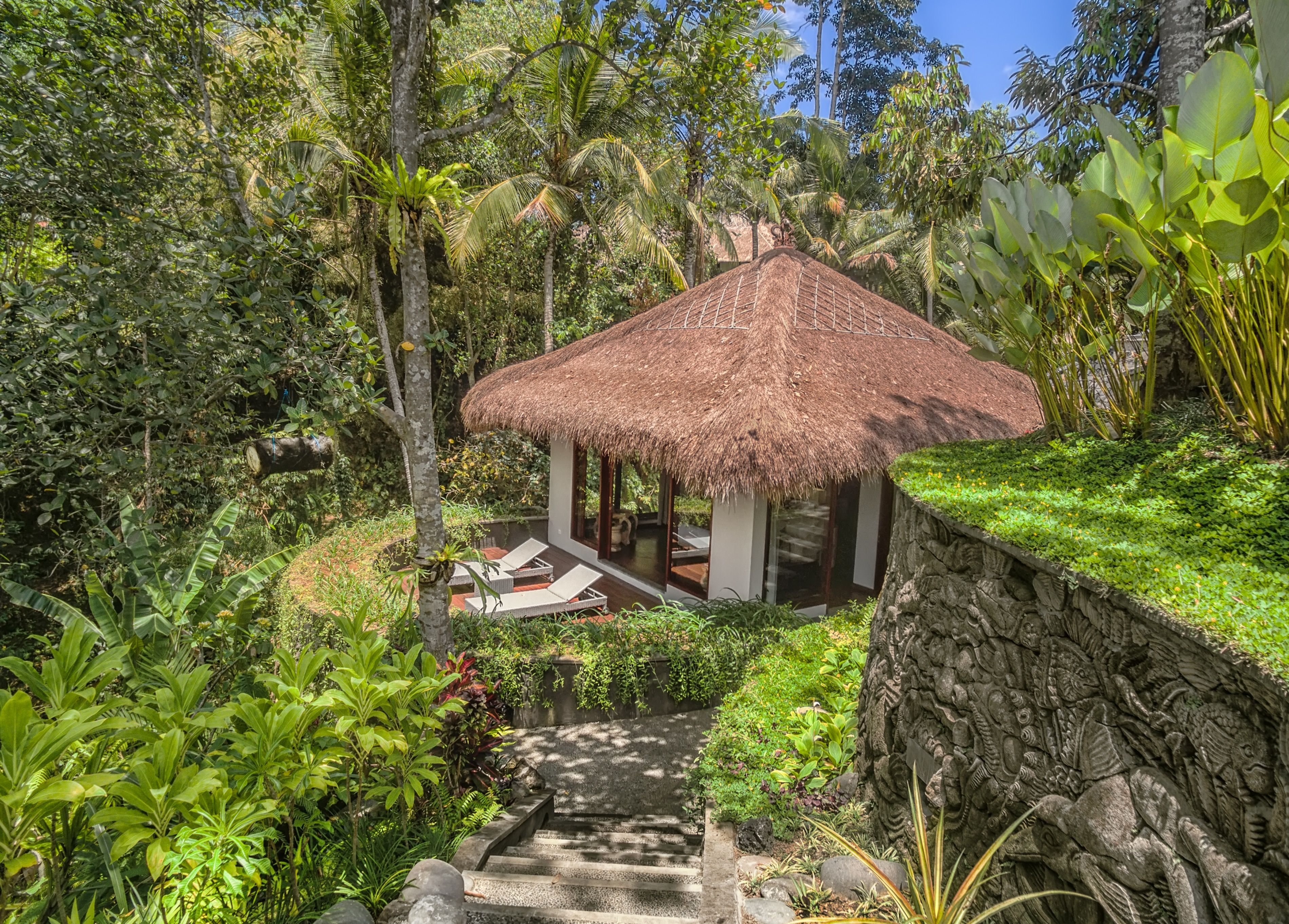 Carved stone walkway at Alam Bulan Villa leads to a private guest ...