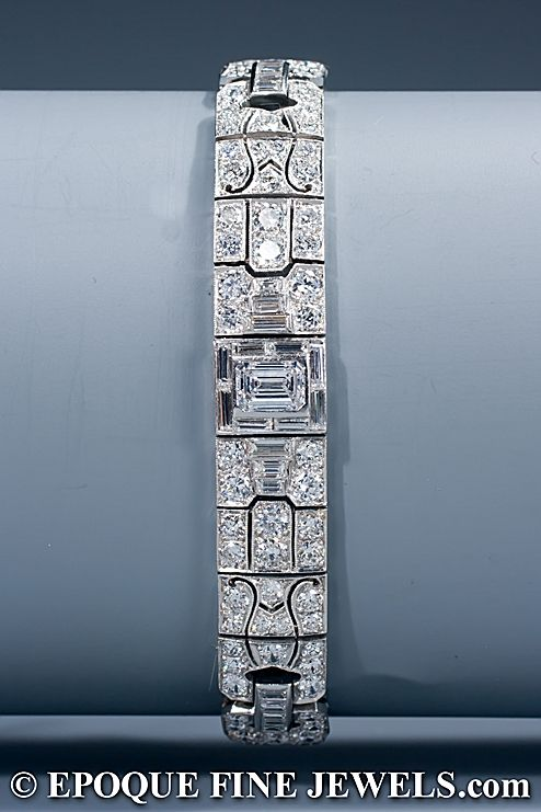 An Art Deco diamond bracelet, centered by an emerald cut diamond weighing approx 0,90 carat, in a baguette cut diamond surround. The platinum openwork mount with 'mille grains' finish is set with old European cut and baguette cut diamonds. American, circa 1930