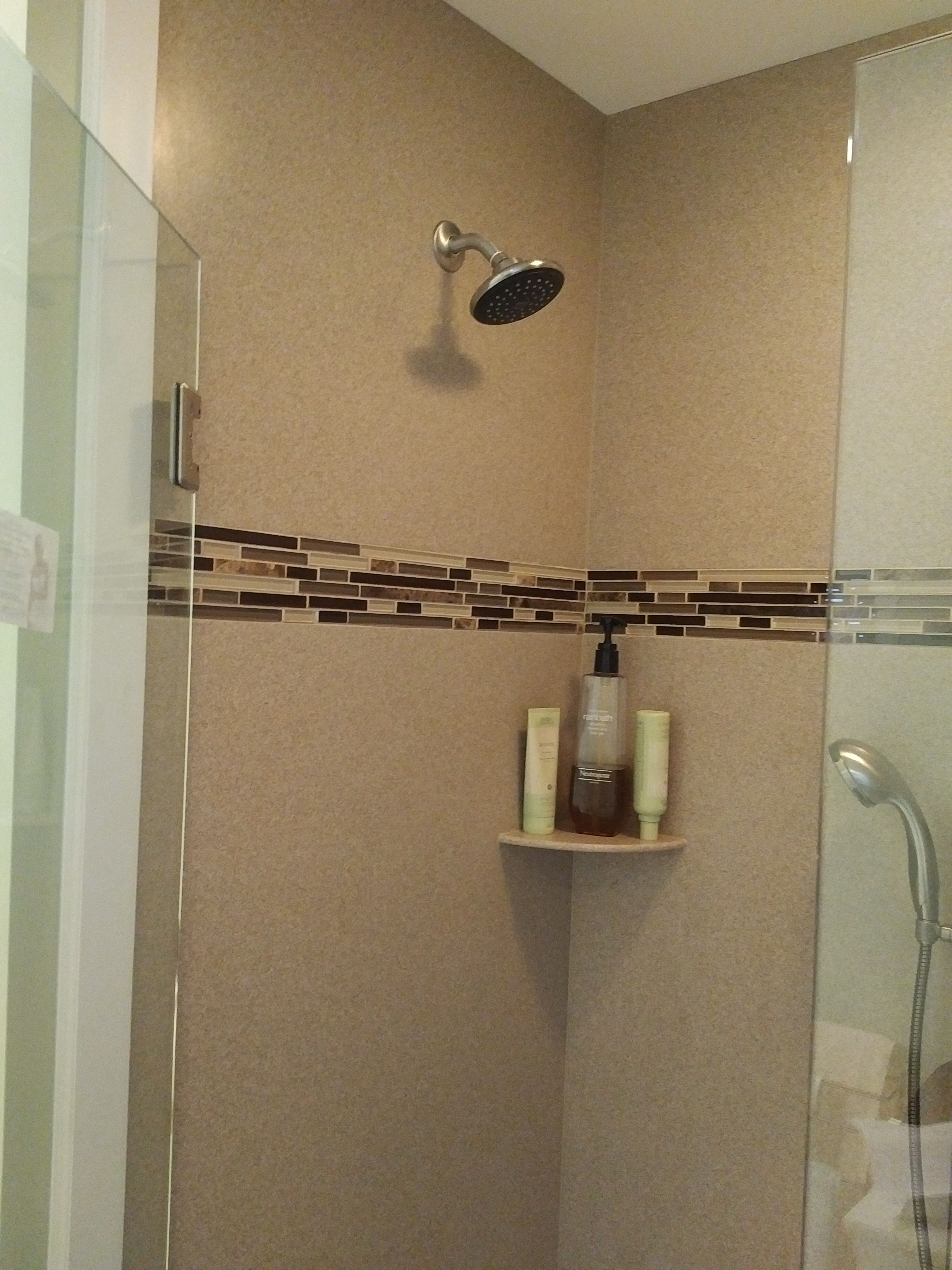 Custom Corian shower surround with decorative tile inset and corner ...