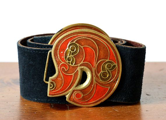 A very uniquely decorated, vintage 1970s, art deco style, brass enamel painted buckle and blue suede belt. The buckle has some nice weight to it and is painted with bursts of umbra, amber and green tones. Paired with a rich, dark, navy, midnight blue belt. The belt is set to a specific size but can be adjusted. Mainly smaller. It is set nearly at its longest. There is about 1 cm on each side of give. Or you can add your own belt. Changing it out seems pretty straight forward. This is the…