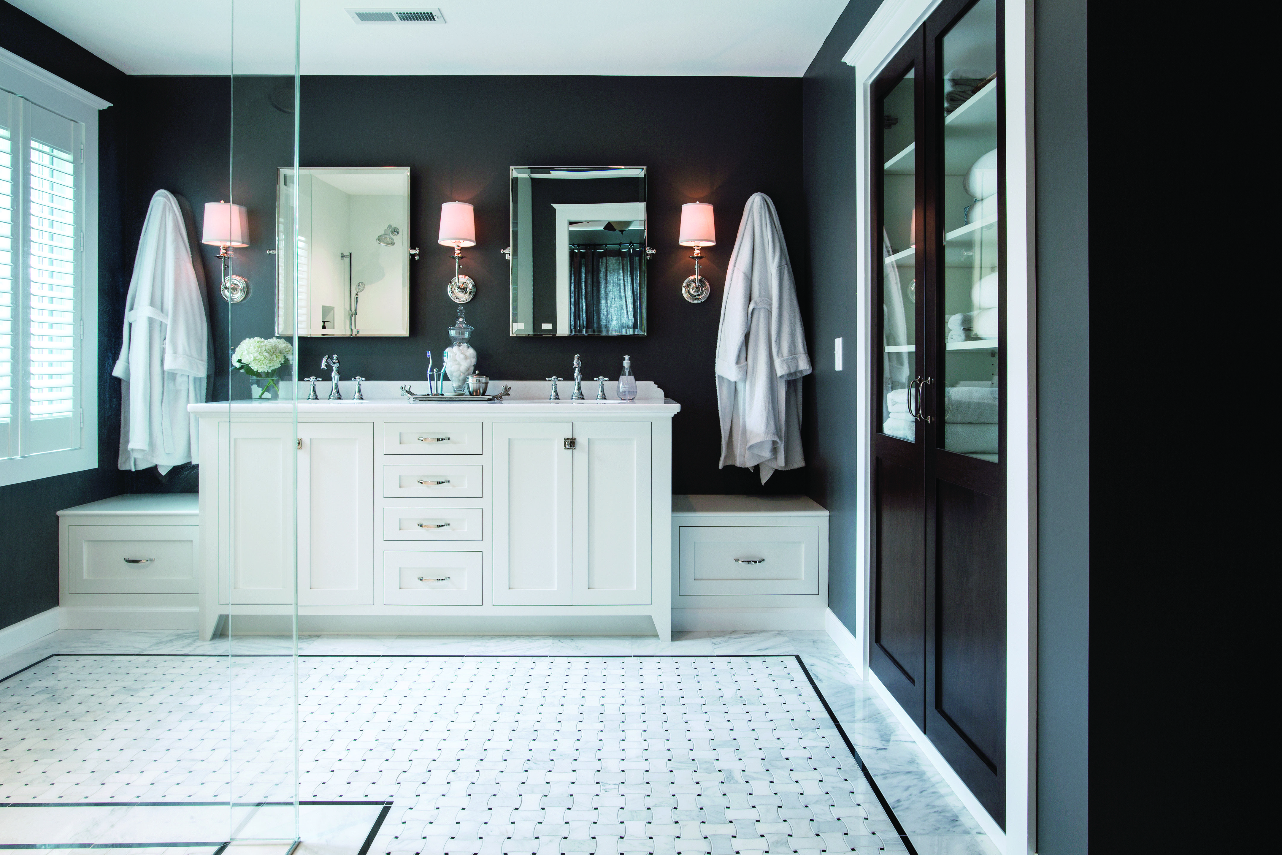 The white vanity and tile flooring with black granite accents keep