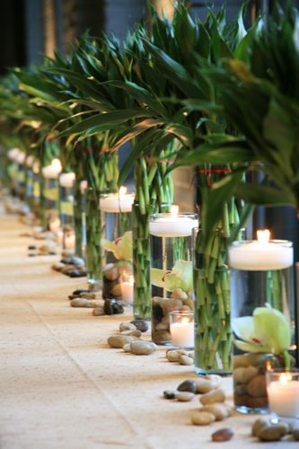 tablescape of bamboo and floating candles with river rocks at the