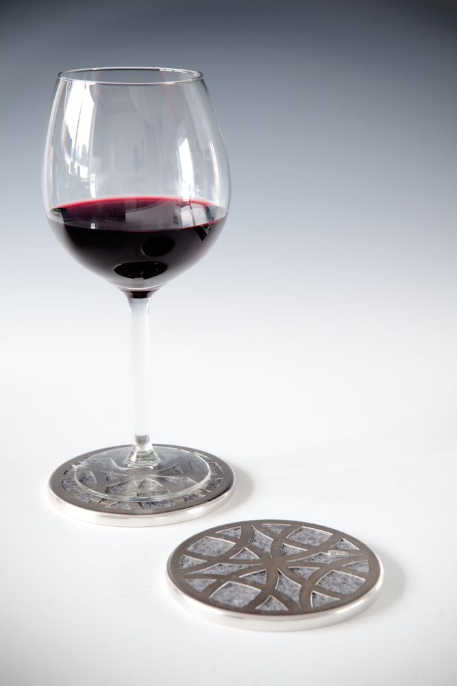 CIRCA Coasters: Silver Plate - The lattice design of these coasters is taken from a section of the overall pattern of interlocking circles that forms the basis of each piece in this collection and has been carefully hand pierced out of copper sheet before being spun around the felt that peeps out through the little windows and acts as a soft base to protect your table. Photograph: In Two Dimensions Photography.