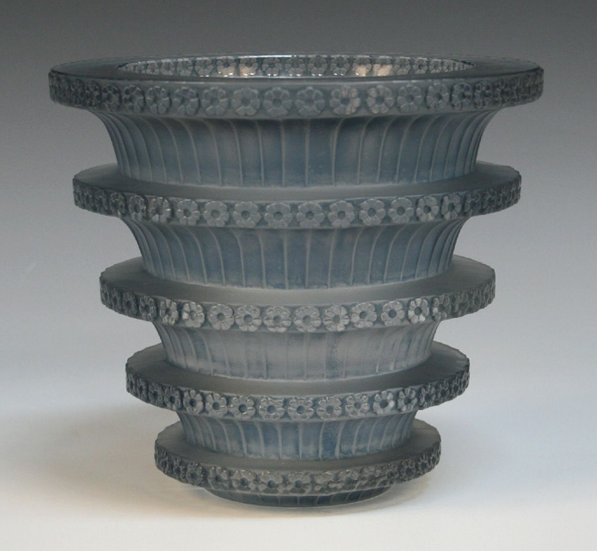 An Art Deco Lalique frosted and blue stained Chevreuse pattern vase, 1930s, of flared cylindrical shape with five horizontal convex bands moulded with flowerhead decoration, acid etched mark to base 'R. Lalique France', height approx 16cm.