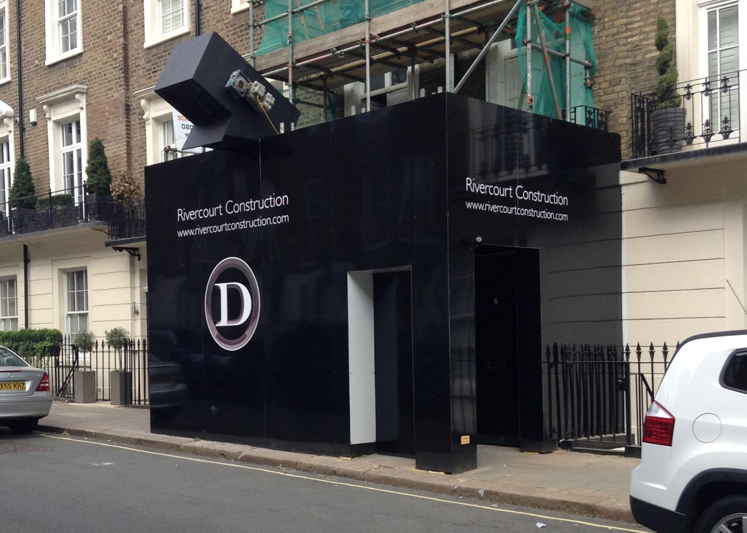 Lavastar gloss black bespoke hoarding design and install. Rivercourt construction hoarding. London hoarding design.