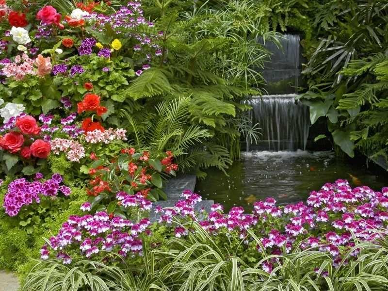 Üppige Garten Gestaltung mit Blumen an einem Teich mit Wasserfall ...