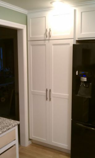 White Pantry Beside A Black Fridge Kitchen Cabinet Door Styles Shaker Kitchen Doors White Shaker Kitchen