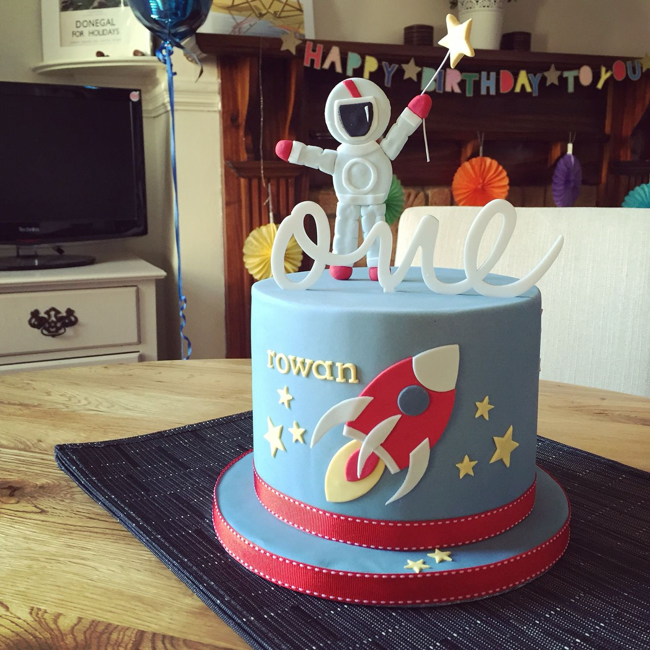 Space themed first birthday cake with stars astronaut and rocket by