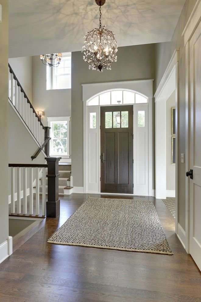 Gorgeous Entryway With High Ceilings Tall Front Door Dark Wood Floors And Open Stairway