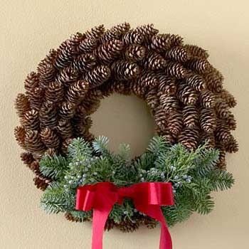 Use hot-glue to attach pine cones around the wreath -- starting in the inside and working your way out. Evergreen sprigs and a bright red ribbon complete this traditional and elegant design.