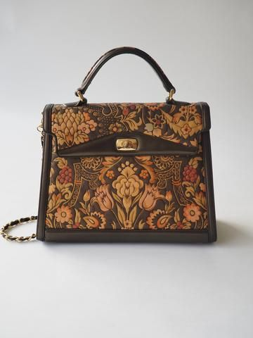 A gorgeous vintage piece featuring florals, a gorgeous chain strap, and a beautiful shape! There...