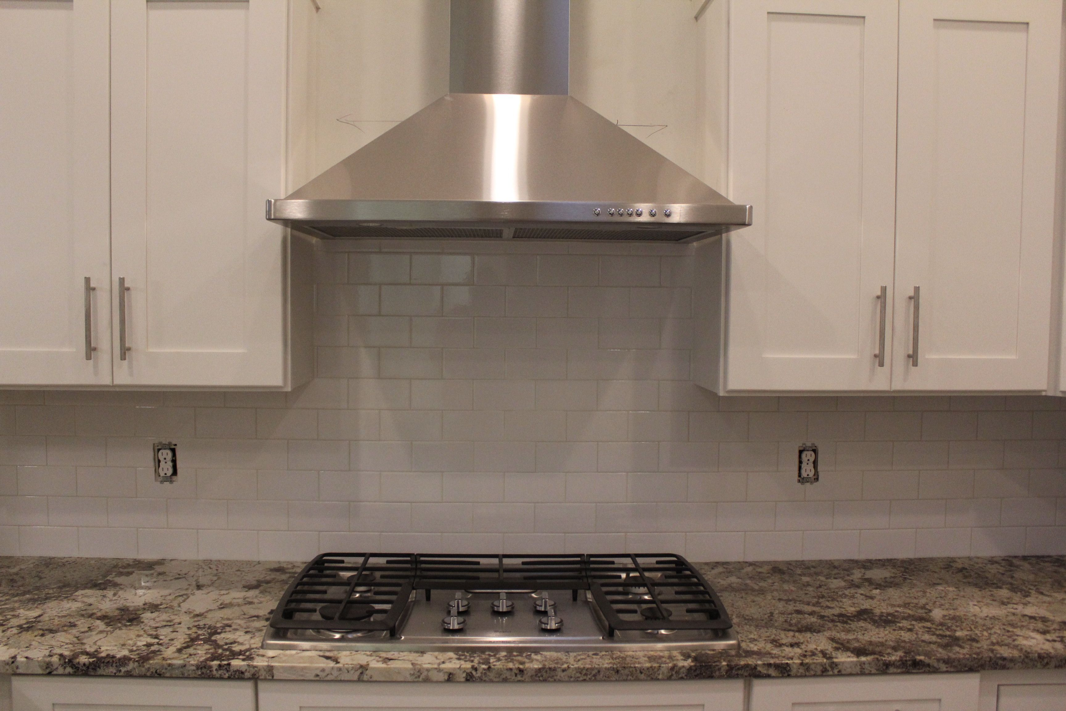 White subway tile backsplash 42 upper custom white kitchen white subway tile backsplash upper custom white kitchen cabinets stainless steel chimney style vented range hood gas cooktop and granite countertops dailygadgetfo Images