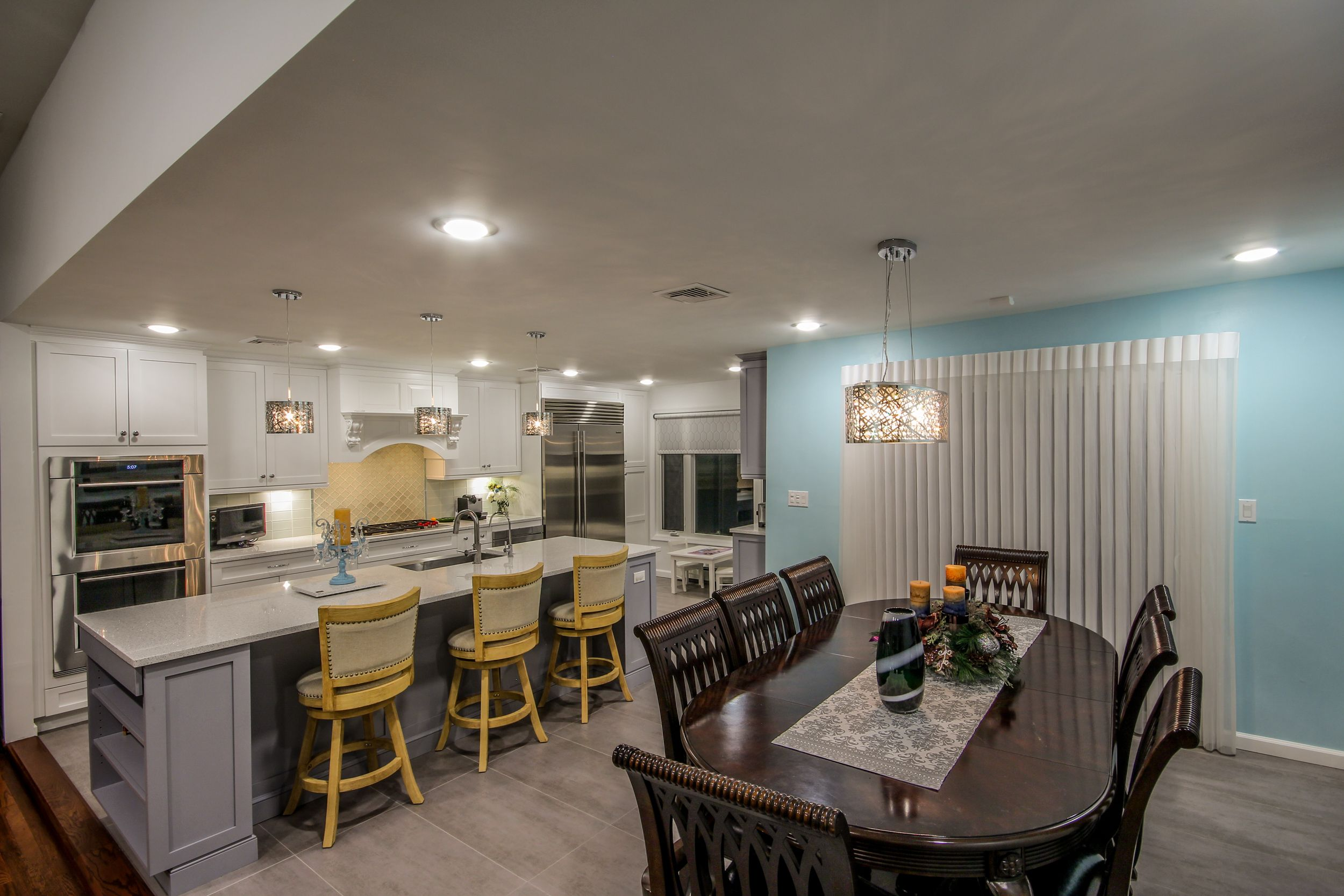 The previously formal dining room is now open and accessible but still maintains a sophistication complete with lighting that is independent, dim-able, and higher end complimented with matching pendants over the island.