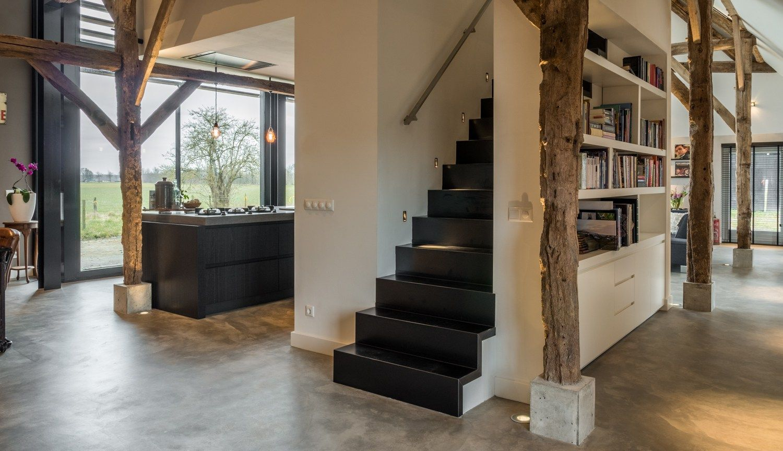 Een strakke stalen trap geeft achter de kastenwand van de keuken