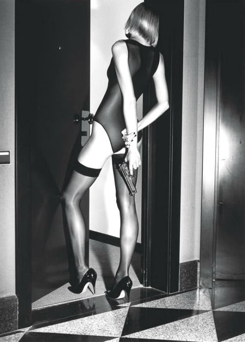 Woman with gun behind her back by Helmut Newton