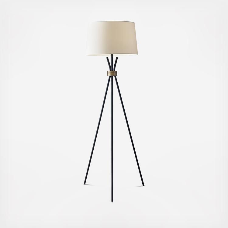 A striking silhouette with minimal elements, the Benson floor lamp is a tripod of black metal legs gathered at the neck with an antique bronze accent. It is topped with a modified drum shade in contrasting off-white linen. A black fabric cord completes the modern statement.