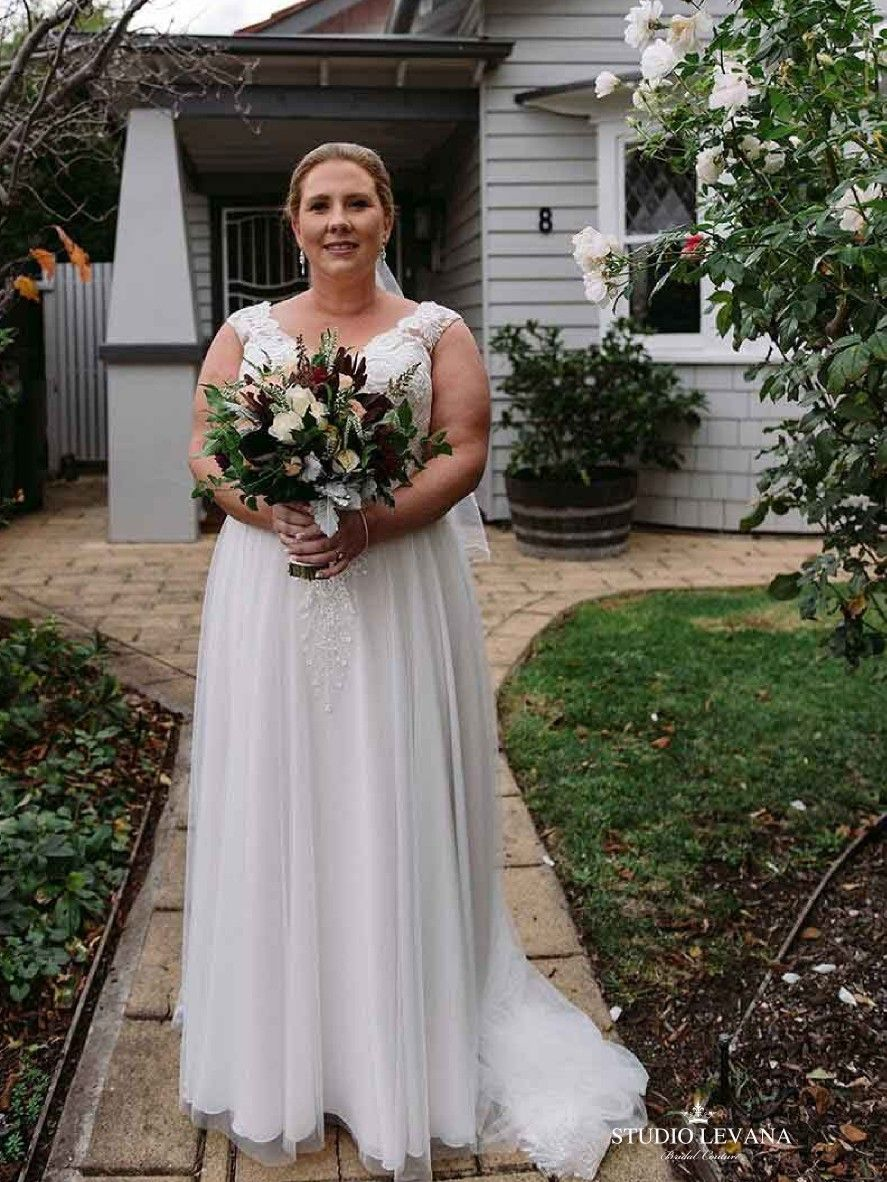 Real bride in a plus size romantic boho wedding gown from studio