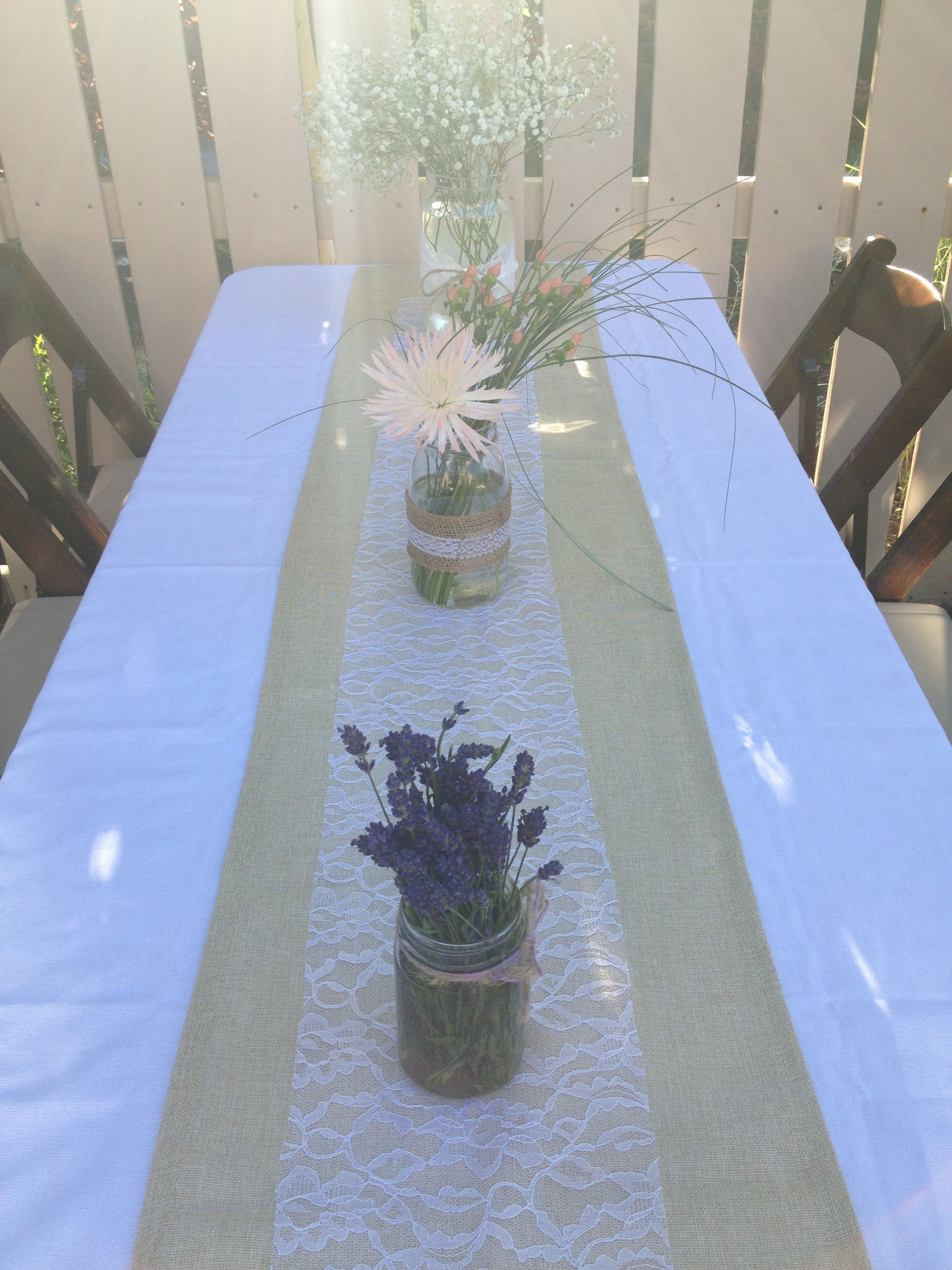 Table runner with lace, mason jar centerpieces with baby's