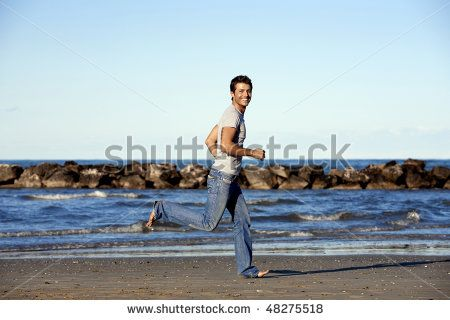 Young man running on beach - stock photo