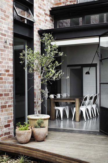 un interieur ouvert sur une terrasse le tout dans un style industriel avec briques et verriere