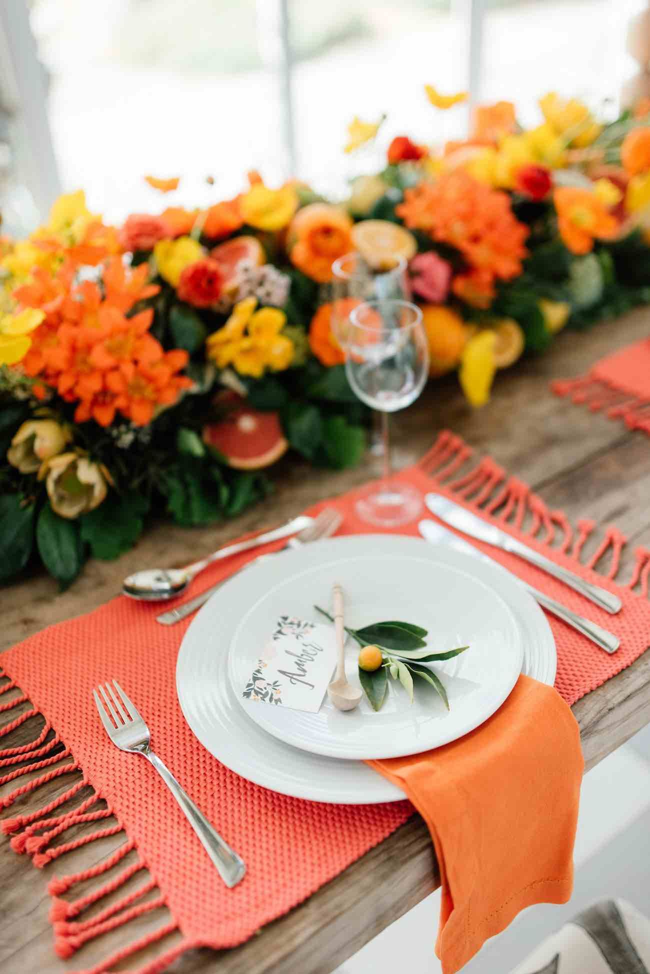 Citrus Wedding theme: place setting at gorgeous tablescape of orange, yellow and green flowers!