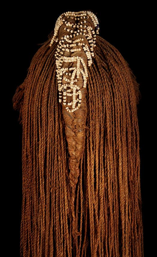 *|* Woman's braided wig from Angola. Mubukush People.  Early 20th century.  Made of strands of woven bush fiber resembling human hair, each of which is attached to a piece of leather hide on the interior.  Two rows of clustered fiber on the front, make for lavish and full bangs.  The central crest is adorned with beaded fringe of white, black, red and blue which terminates into a long elegant pigtail!  There is no synthetic materials used whatsoever.